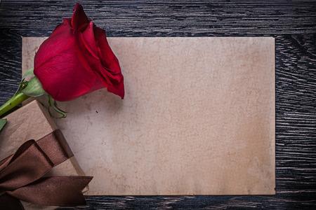 birthday greetings: rojo de la rosa de papel de la vendimia caja de regalo envuelta en la tabla de madera.