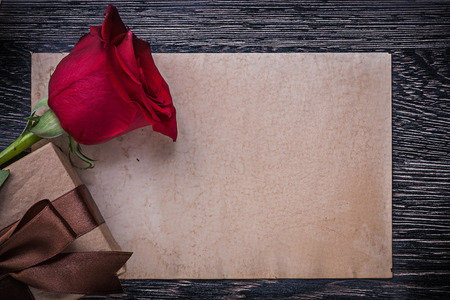 birthday presents: Vintage paper red rose wrapped gift box on wooden board.