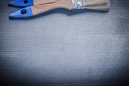repaint: Paintbrushes with wooden handles on wood board construction concept. Stock Photo