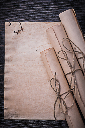 corded: Vintage corded paper scrolls on wooden board.