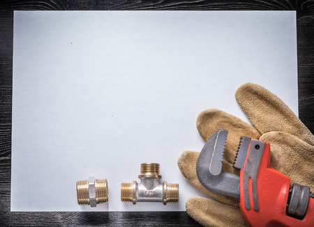pipe wrench: Pipe wrench brass plumbing fittings leather safety gloves white paper.