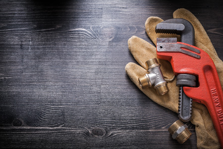 Pipe wrench plumbing fixtures protective gloves on wooden board. Stock Photo