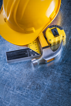 square ruler: Square ruler measuring tape protective hard hat and claw hammer on scratched metallic surface construction concept. Stock Photo