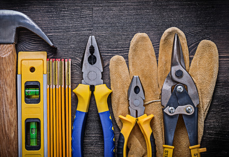construction level: Safety gloves pliers tin snips wooden meter construction level hammer.