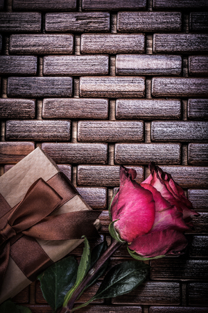matting: Red fragrant rose wrapped giftbox on wicker wooden matting.