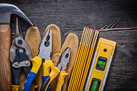 snips: Protective gloves pliers tin snips wooden meter construction level hammer. Stock Photo