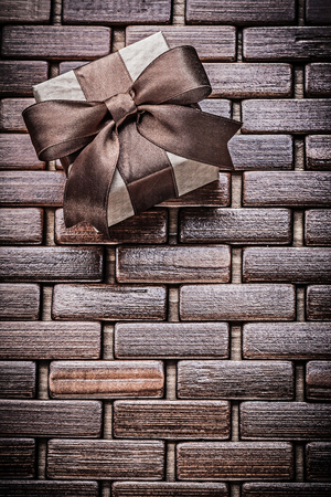 wrapped present: Wrapped present box on wooden wicker place mat holidays concept.