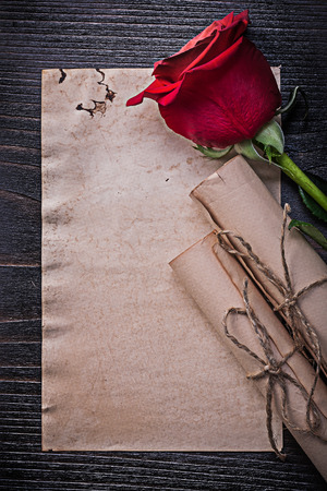 felicitaciones cumplea�os: Vintage corded paper rolls red bloomed rose on wooden board. Foto de archivo