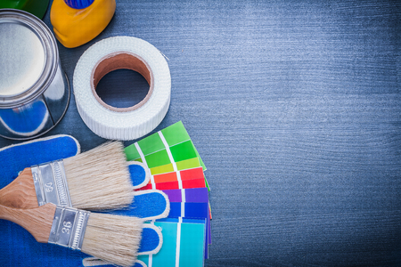 sampler: Paint containers color sampler protective gloves paintbrushes adhesive tape. Stock Photo