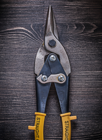 snips: Metal sharp tin snips on wooden board construction concept.