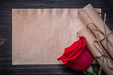 corded: Vintage corded paper scrolls red expanded rose on wooden board. Stock Photo