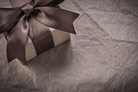 giftbox: Birthday giftbox with brown bow on wrapping paper holidays concept.