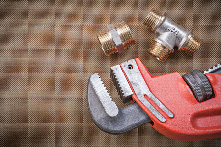 household fixture: Adjustable wrench brass connector fittings on cleaning mesh filter grid. Stock Photo