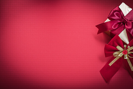 giftbox: Christmas bow giftbox on red background holidays concept. Stock Photo