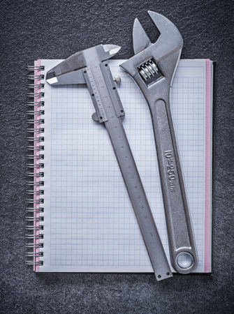 caliper: Adjustable wrench slide caliper notebook on black background construction concept.