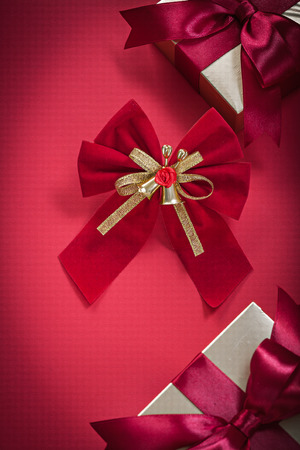 wrapped present: Christmas bow wrapped present boxes on red background holidays concept.