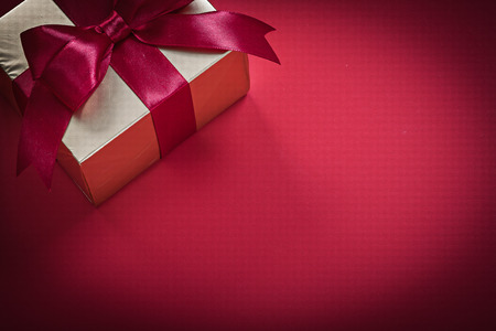 giftbox: Giftbox with ribbon on red background holidays concept.