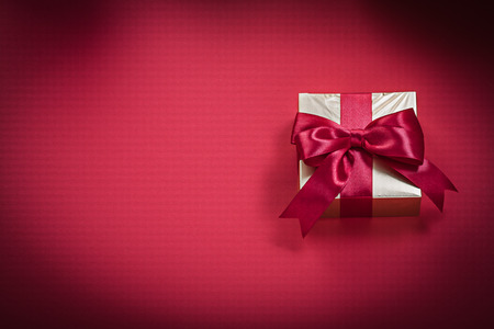 giftbox: Giftbox with tied bow on red background holidays concept.