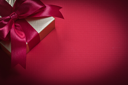 wrapped present: Wrapped present box on red background holidays concept. Stock Photo