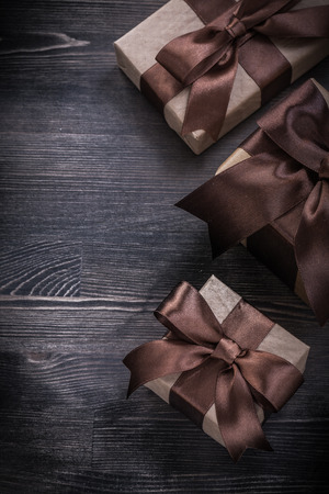 goldish: Present boxes with tied ribbons on wooden board holiday concept.