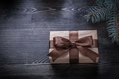 goldish: Pine branch wrapped gift box on wooden board holiday concept. Stock Photo