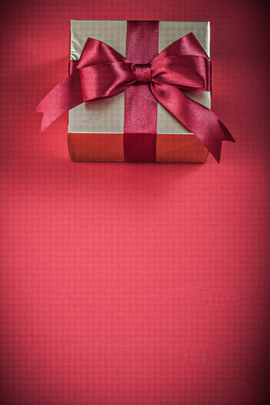 red glittery: Packed gift container with bow on red background holidays concept.