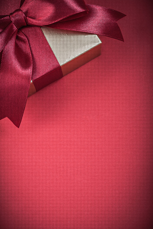 giftbox: Packed giftbox on red background holidays concept. Stock Photo