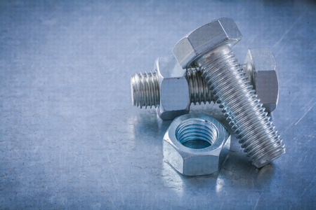 threaded: Stainless threaded bolts screw-nuts on scratched metallic background maintenance concept.