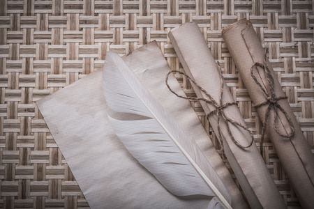 pack string: Rolls of vintage paper clean sheet feather on wicker mat.