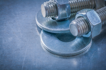 threaded: Threaded bolt washers screwbolts construction nuts on metallic background. Stock Photo