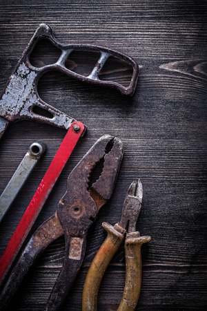 wire mess: Rusty vintage handsaw wire-cutter pliers on wooden board construction concept. Stock Photo
