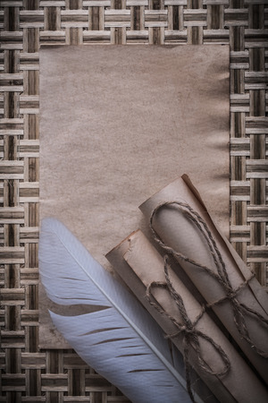 page background: Medieval blank sheet rolled paper quill on wicker wooden background.
