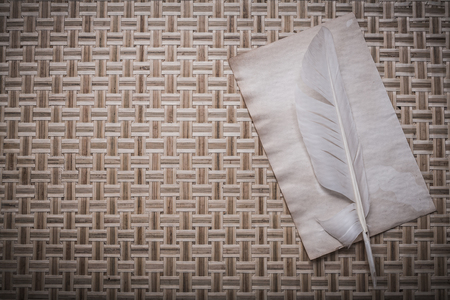 matting: Vintage clean sheet of paper plume on wicker wooden matting.