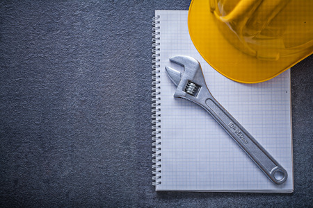 Notebook hard hat adjustable wrench construction concept.