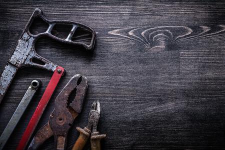 serrucho: Rough vintage handsaw wire-cutter pliers on wooden board construction concept. Foto de archivo