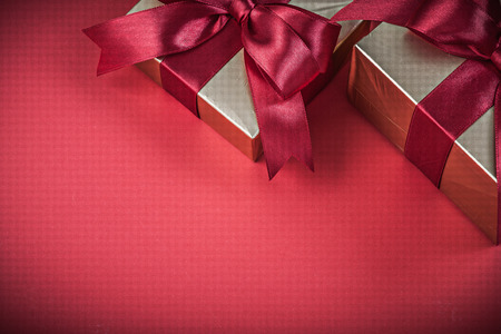 red glittery: Present boxes on red background horizontal view holidays concept. Stock Photo