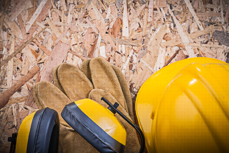 leather gloves: Safety leather gloves building helmet earmuffs on chipboard. Stock Photo