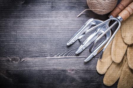 hank: Trowel fork rake leather gloves hank of rope agriculture concept.