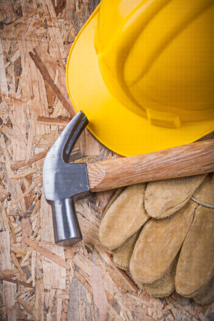 leather gloves: Claw hammer building helmet leather gloves on chipboard construction concept. Stock Photo