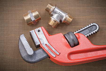 household fixture: Monkey wrench brass connector fittings on cleaning mesh filter grid. Stock Photo