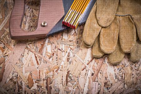 serrucho: guantes de cuero de protección serrucho madera de un metro sobre tablero aglomerado. Foto de archivo