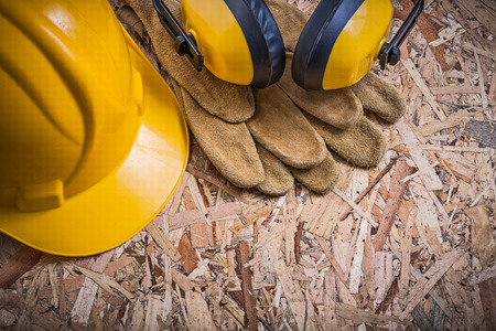 protectors: Protective leather gloves hard hat ear protectors on OSB.