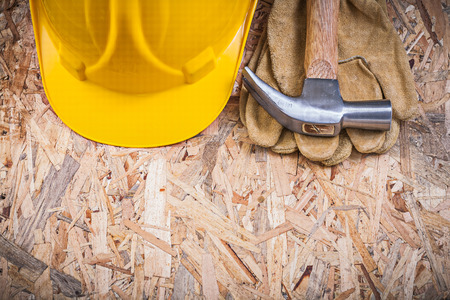 chipboard: Claw hammer building helmet safety gloves on chipboard construction concept. Stock Photo
