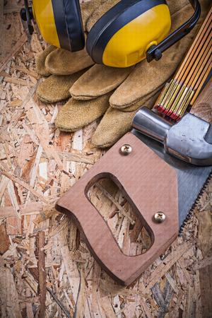 serrucho: Protective gloves wooden meter handsaw claw hammer earmuffs on OSB. Foto de archivo