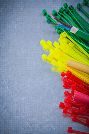 dielectric: Composition of plastic cable ties on scratched metallic background. Stock Photo