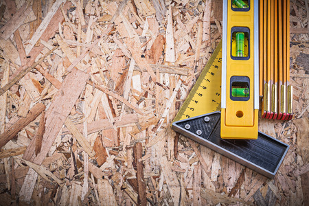 Square ruler construction level wooden meter on OSB.