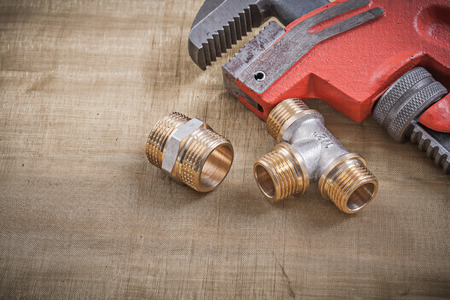 household fixture: Plumbers wrench plumbing fixtures on mesh filter grid. Stock Photo