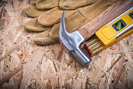 osb: Claw hammer safety gloves construction level wooden meter on OSB. Stock Photo