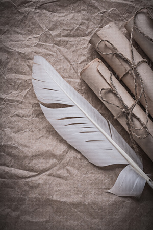 pack string: Heap of vintage paper rolls feather on crumpled wrapping sheet. Stock Photo