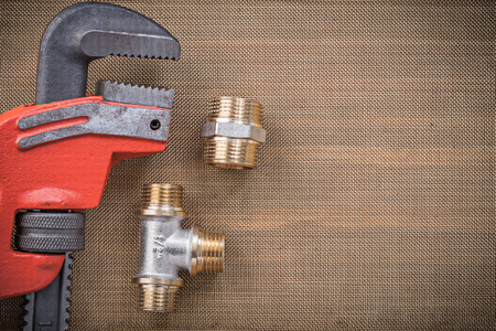household fixture: Plumbers wrench brass connector fittings on cleaning mesh filter grid. Stock Photo